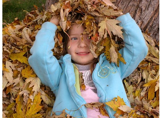 little girl in leaf pile